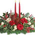 Send your holiday wishes with style! This beautiful Christmas centerpiece features velvety red and white roses, pine cones, and more nestled in fresh evergreens and crowned with twin taper candles. It?s a great way to set the table and warm hearts, too. Available after Thanksgiving till Christmas. Same day and next day florist delivery in the USA and Canada.