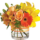 Send smiles across miles with this cheery bouquet of sunny yellow and orange blooms nestled in a compact glass vase. Featured flowers include lilies, Gerberas, roses, alstroemeria, or similar fresh favorites. Popular throughout summer and Fall. Approximately 8 to 10 inches in height. USA and Canada florist delivery.