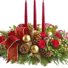Adorn someone's table with this classic candle centerpiece featuring fresh evergreens, red miniature carnations, pine cones, ribbon, berries, and golden accents. A holiday tradition with style galore! Available after Thanksgiving through December. USA and Canada florist delivery.