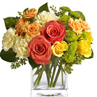 A compact nosegay style bouquet of orange, yellow, and greens, nestled in a contemporary petite glass cube or vase. Great for a desk, counter, or coffee table. Featured flowers include roses, buttons, carnations, miniature roses, or similar favorites. A delight for the eyes! USA and Canada florist delivery.