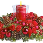 Make their holiday table glow with this beautiful Christmas centerpiece featuring crimson blossoms and ornament balls, pine cones, berries, and winter greens crowned with a festive pillar candle in glass. Lovely! Available in most areas after Thanksgiving through December. Professional florist design and delivery in the USA and Canada.